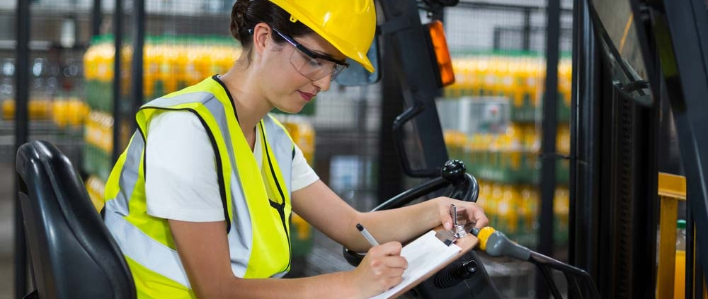 Female factory worker sitting on forklift and writing on a clipboard.