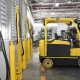 Recharging an electric forklift in a warehouse room.