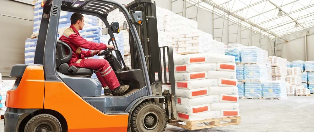 Forklift driver stacking pallets with cement packs by stacker loader.