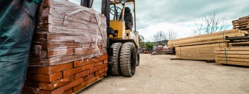 A forklift carrying construction materials including clay and bricks at a building site.